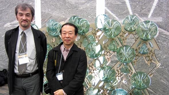 環境情報学部の小川克彦教授(右)と政策・メディア研究科の池田靖史教授。後方のオブジェは池田研究室の「ガラス玉ウォール」で、東日本大震災の被災地である気仙沼(宮城県)で浮きとして使われていた漁業用のガラス玉を1つ1つKinectで測定し、それぞれの形に合わせて木板を切り出した