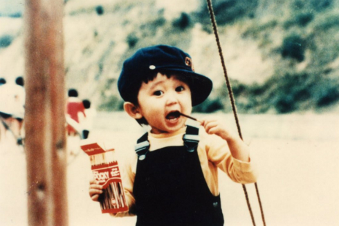ポッキーを食べる子どものころの有吉弘行さん