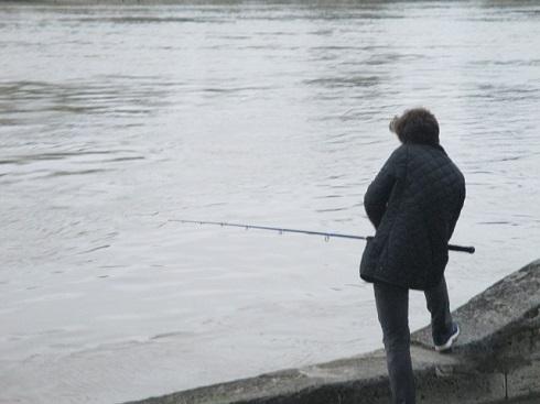 増水したセーヌで釣りをする人