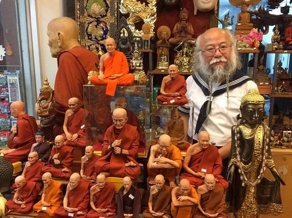 お土産屋さんの中、タイの有名な僧侶の像に囲まれるセーラー服おじさん……意外と馴染んでいる