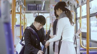 女性が学生に傘を渡す様子