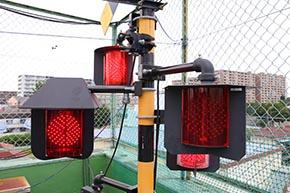 踏切警報機柱(アルミ形)に装着された、踏切警標と全方向踏切警報灯 LED III形。そのうち1つ(左)はオプションの防雪フード付き