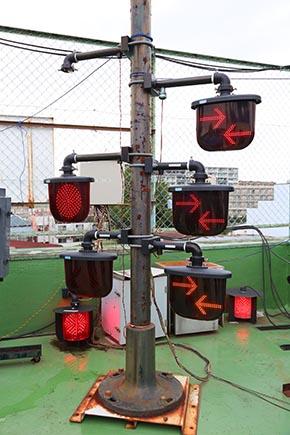 両面形の踏切警報灯 eco1シリーズ(左2つ)と踏切警報灯列車進行方向指示器 eco1(右3つ) 無造作に床置きされつつも発光テスト継続中の全方向踏切警報灯も2つ