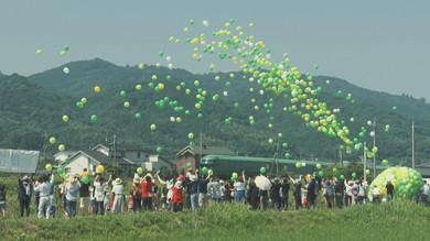 風船で運転再開を祝う人々