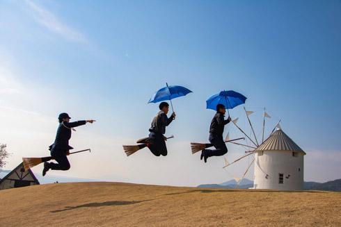 傘を差しながらホウキに乗る男