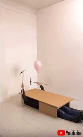箱の中から鎌を振って風船を割る