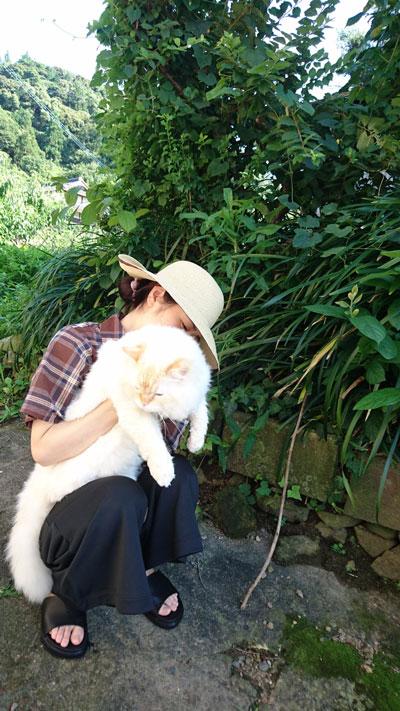 座る飼い主さんに抱っこされるハクさん