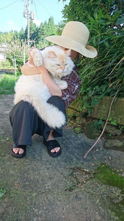 座る飼い主さんに抱っこされて正面を向くハクさん