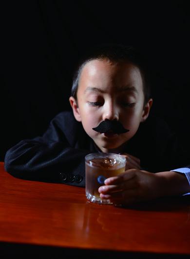 子どもがロックグラスでお茶を飲む様子