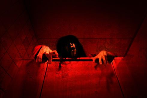 全体に赤みを帯びたトイレのうえから幽霊が顔を出している写真