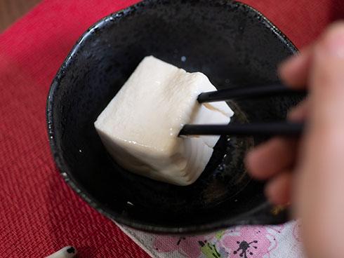 四角い湯豆腐を箸ですくうところ