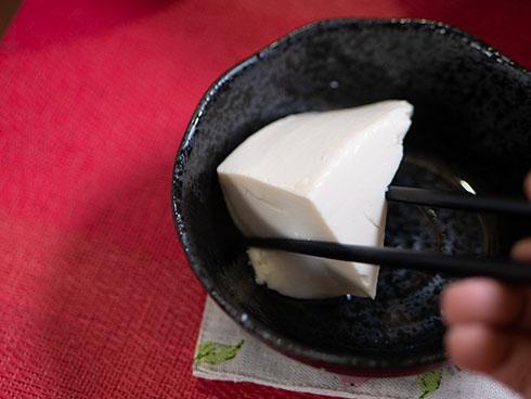 三角の湯豆腐を箸ですくうところ