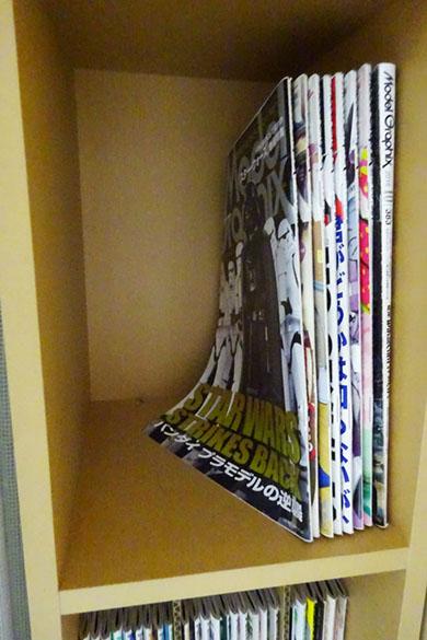 本棚に模型誌が並べられ手前の本がぐにゃっと倒れかけている