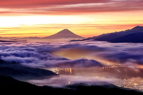 朝焼けの富士の麓に広がる雲海の下に街の灯り