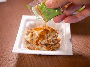 生姜焼納豆にタレを入れるところ
