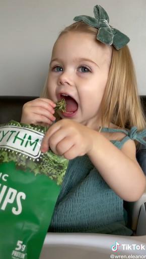 ケールチップスを食べる女の子