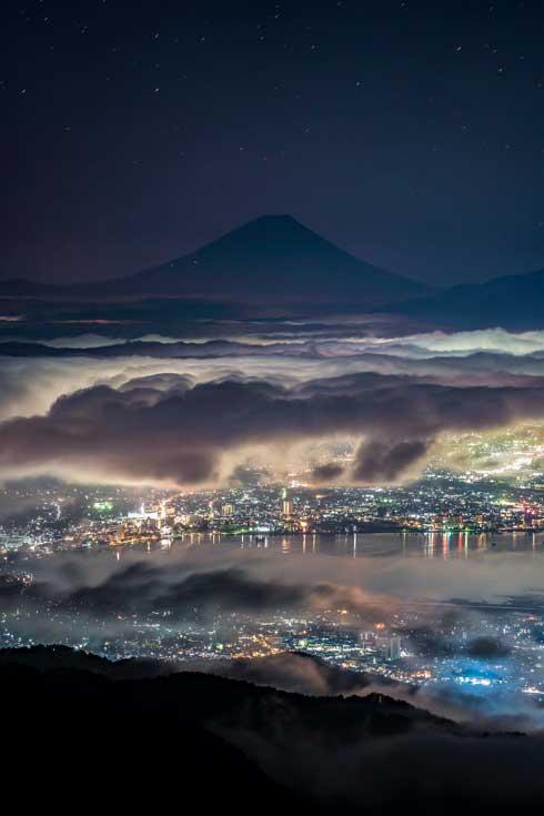 雲の上から街を見守る 富士山 写真