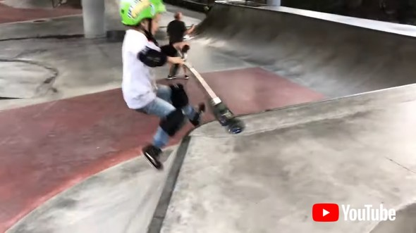 Little Kid Shows Tricks On Scooter While Practicing For Competition In Skatepark