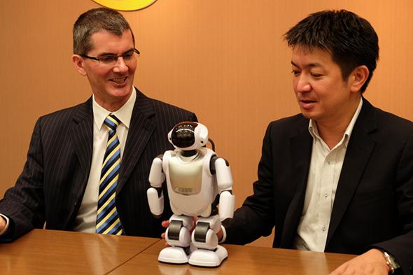 日本セーフネットのIDSSソフトウェアマネタイゼーション事業部Vice Presidentのジェラード・ポールクラーク氏(左)とDMM.com ロボット事業部事業部長の岡本康広氏(右)。中央はDMM.make ROBOTSで販売されている富士ソフト製コミュニケーションロボット「Palmi」