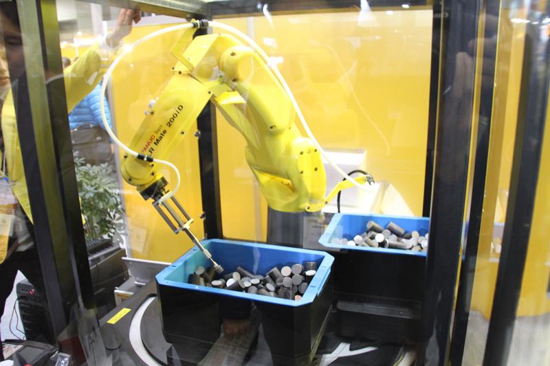 ディープラーニングと製造業」で最も有名な応用例は、Preferred Networksとファナックが協力して実現した、ピッキングロボットの事例でしょう。ロボットが「バラ積みされた部品のどこを空気吸引でつかむべきか」を、自分で取得した大量の画像データ(とその結果)を利用して学びとります(写真は「2015 国際ロボット展」にてファナックが行ったピッキングロボットのデモ)