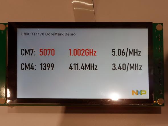 写真2:Cortex-M7とM4の両方のコアでCoreMarkを実施している結果が、トータル6400CoreMarkオーバーというスコアになっている。ちなみに「触ってみてもいいぞ」というので動作中にi.MX RT 1170に触れてみたが、ほんのり温かい程度。実際ヒートシンクもなしに稼働していた
